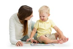 Madre que hace jugando el juguete del rompecabezas así como su hijo del niño en el piso aislado en el fondo blanco foto de archivo libre de regalías