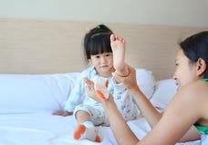 Madre que intenta poner los calcetines para su hija en la cama imagen de archivo libre de regalías
