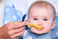 Madre que introduce al bebé hambriento Imagen de archivo libre de regalías
