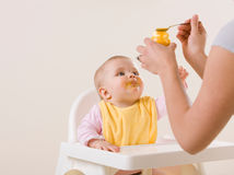Madre que introduce al bebé hambriento en highchair Imagenes de archivo