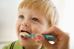 Madre que introduce los alimentos para niños jovenes del muchacho imagen de archivo libre de regalías