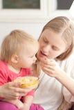 Madre que introduce a su hija con las gachas de avena Imagen de archivo
