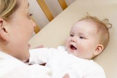 Madre que juega con el bebé en choza Imagenes de archivo