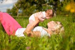 Madre que juega con el bebé en prado Fotografía de archivo libre de regalías