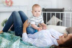 Madre que juega con el bebé que miente en cama Fotos de archivo