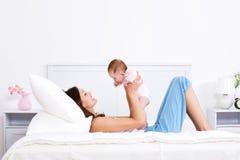 Madre que juega con el bebé en la cama Fotografía de archivo