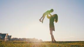 Madre que juega con el pequeño niño en la puesta del sol - tiros el hijo Imagen de archivo