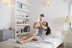 Madre que juega con la hija del bebé en dormitorio en casa Imagen de archivo