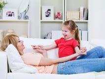 Madre que juega con la hija en el sofá Imágenes de archivo libres de regalías