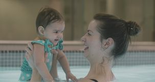 Madre que juega con su bebé en la piscina almacen de video
