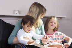 Madre que lee a los niños en cama imagenes de archivo