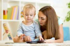 Madre que lee un libro al niño en casa imagen de archivo libre de regalías