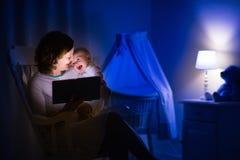 Madre que lee un libro al pequeño bebé Fotos de archivo libres de regalías
