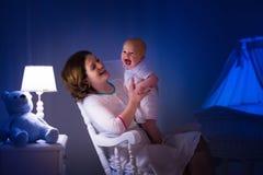 Madre que lee un libro al pequeño bebé Fotos de archivo