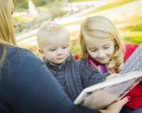 Madre que lee un libro a sus dos niños rubios adorables imagen de archivo