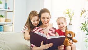 Madre que lee un libro a sus hijas fotografía de archivo