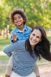 Madre que lleva a cuestas al hijo en el parque Fotografía de archivo