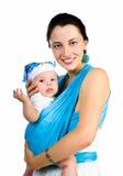 Madre que lleva a su bebé en una honda imagen de archivo libre de regalías