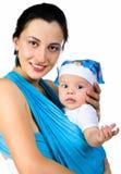 Madre que lleva a su bebé en una honda imagen de archivo