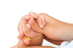 Madre que mantiene la mano de su bebé unida Fotografía de archivo