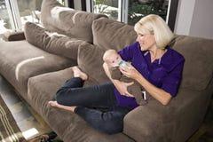 Madre que mira cariñosamente la botella de consumición del bebé Fotografía de archivo libre de regalías