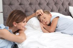 Madre que mira a su hijo dormir en cama fotos de archivo