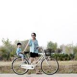 Madre que monta una bicicleta con su hijo foto de archivo libre de regalías