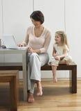 Madre que muestra el ordenador portátil de la hija Foto de archivo