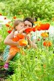 Madre que muestra las flores a la hija Imagen de archivo libre de regalías