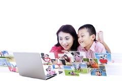 Madre que muestra las fotos digitales aisladas en blanco Imagen de archivo