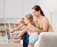 Madre que muestra a niños la computadora portátil fotografía de archivo libre de regalías