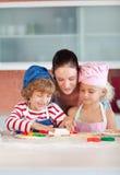 Madre que obra recíprocamente con los niños en cocina Imagen de archivo libre de regalías
