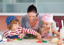 Madre que obra recíprocamente con los niños en cocina Fotos de archivo libres de regalías