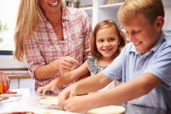 Madre que prepara la pizza con los niños Foto de archivo libre de regalías
