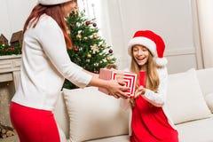 Madre que presenta el regalo de la Navidad para la hija Fotos de archivo