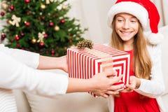 Madre que presenta el regalo de la Navidad para la hija Imagen de archivo