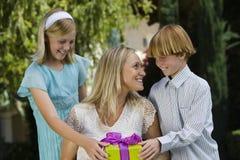 Madre que recibe el regalo de niños Fotografía de archivo libre de regalías