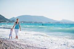 Madre que recorre con el bebé en la costa Fotos de archivo libres de regalías