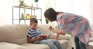 Madre que regaña al hijo que juega al juego en el teléfono móvil almacen de video
