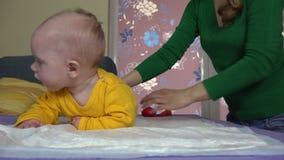 Madre que se prepara para dar masajes a la pequeña hija del bebé 4K almacen de video