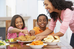 Madre que sirve una comida a sus niños