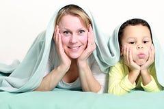 Madre que sonríe con el niño y que se divierte junto fotografía de archivo libre de regalías