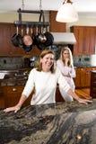 Madre que sonríe en cocina con la hija adolescente Fotografía de archivo