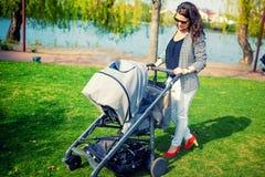 Madre que sonríe con el bebé en parque Mime al niño que camina con el cochecito de niño o el cochecito de bebé Imagen de archivo libre de regalías
