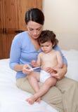 Madre que toma a bebés temperatura Fotografía de archivo