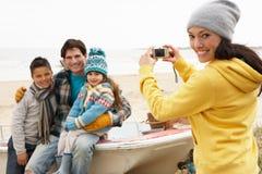 Madre que toma la fotografía de la familia en la playa del invierno Imagen de archivo libre de regalías
