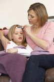 Madre que toma temperatura de la hija enferma Imagen de archivo