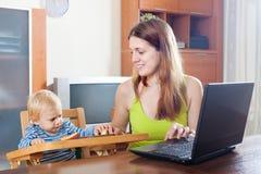 Madre que trabaja con el ordenador portátil y el bebé Foto de archivo