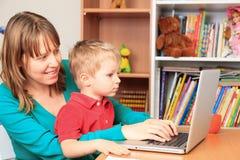 Madre que trabaja de hogar con el pequeño hijo Imagen de archivo libre de regalías