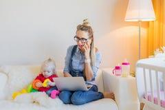 Madre que trabaja en el ordenador portátil en casa Fotografía de archivo